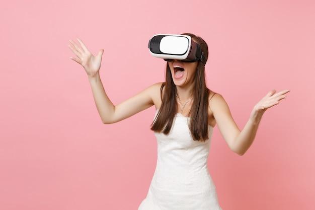 Ritratto di donna stupita in abito bianco, cuffia di realtà virtuale che allarga le mani