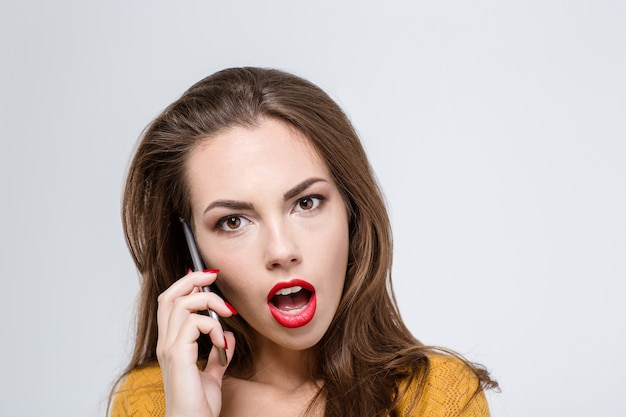 Portrait of a amazed woman with mouth open talking on the phone isolated on a white wall