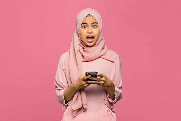 Portrait of amazed young asian woman using a smartphone
