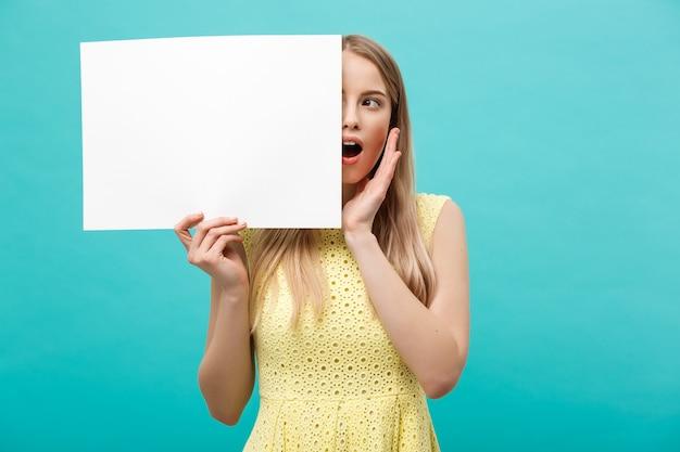 Ritratto di giovane donna bionda stupita che tiene segno in bianco con lo spazio della copia sul fondo blu dello studio. mostrando una faccia scioccata a sorpresa.