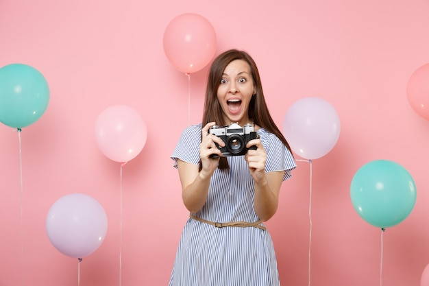 Portrait of amazed young happy woman wearing blue dress holding retro vintage photo camera on bright pink background with colorful air balloons. birthday holiday party people sincere emotions concept.