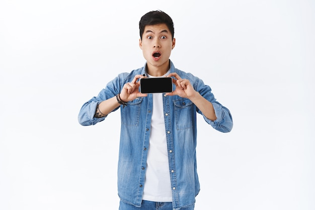 Portrait of amazed young impressed asian man showing new trailer of movie on smartphone screen, holding mobile phone horizontally, open mouth amused