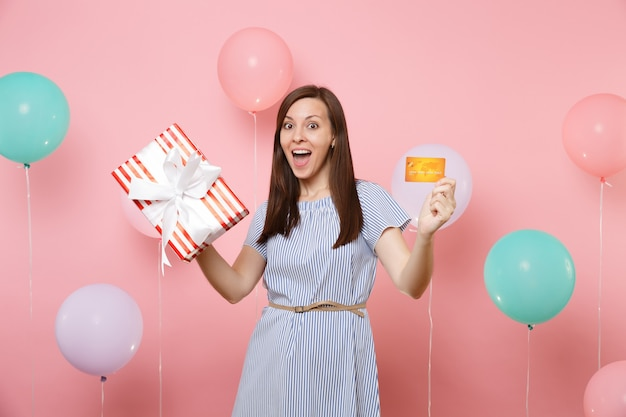 Portrait of amazed young woman in blue dress holding credit card and red box with gift present on pastel pink background with colorful air balloons. birthday holiday party, people sincere emotions.