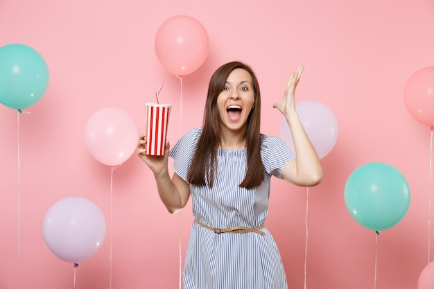 Portrait of amazed young woman in blue dress with opened mouth spreading hands holding plastic cup of cola or soda on pastel pink background with colorful air balloons. birthday holiday party concept.