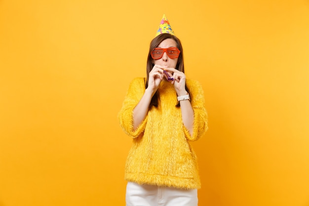 Portrait of amazed young woman in orange funny eyeglasses, birthday party hat with playing pipe celebrating isolated on bright yellow background. people sincere emotions lifestyle. advertising area.