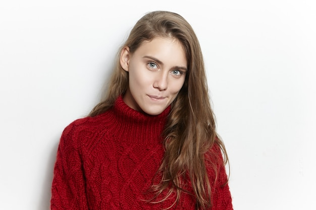 Portrait of amazing gorgeous young european woman with long loose hairstyle posing isolated in cozy marsala pullover, staring with mysterious curious facial expression, biting lips