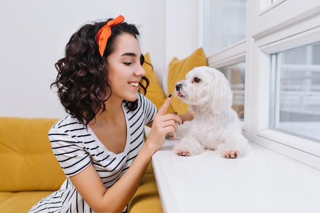 近代的なアパートで小さな犬と遊んで驚くべきうれしそうなファッショナブルな若い女性の肖像画。家庭でのペット、笑顔、陽気な気分、家で楽しむ