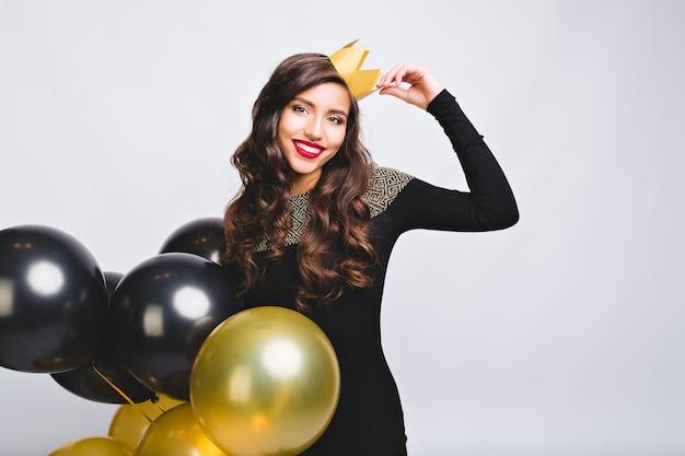 Ritratto incredibile bella donna che celebra le vacanze, che tiene palloncini oro e neri, vestito nero e corona gialla, divertirsi, festa