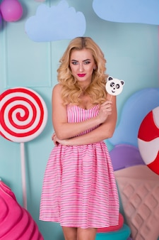 Portrait of amazing sweet-tooth woman in pink dress holding candies and posing on background
