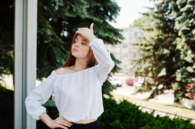 Portrait of an amazing woman in white blouse and wide black pants posing with pine trees