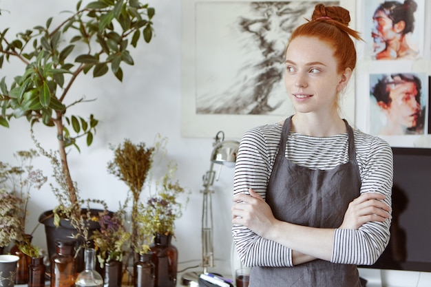 Portrait of amazing young seamstress with ginger hair and freckles wearing apron standing in modern workshop space interior, looking away with dreamy thoughtful smile, keeping her arms folded
