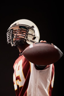 Portrait of american football player showing ball against black background