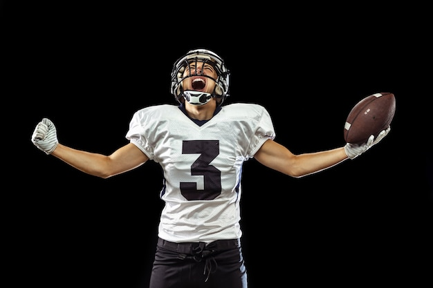 Portrait of american football player in sports equipment isolated on black