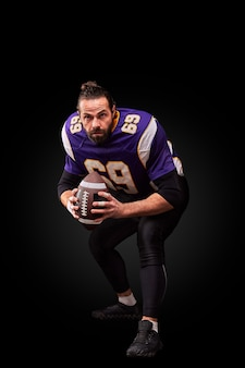 Portrait of american football player throwing ball over black background