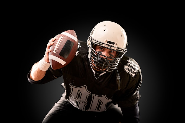 Portrait of american football player with helmet close up, on black background