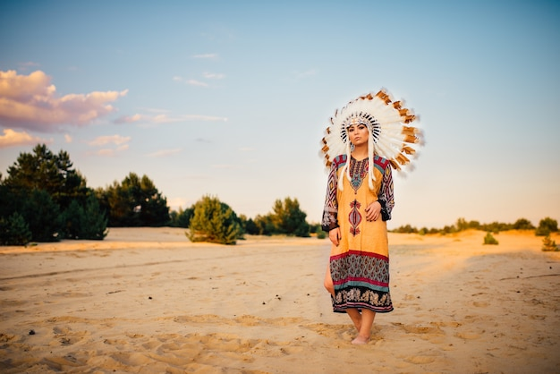 Portrait of american indian girl in traditional costume and headdress made of feathers of wild birds