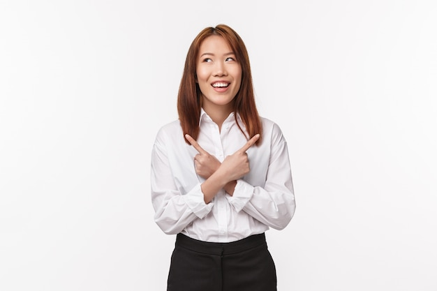 Portrait of amused and dreamy smiling asian woman in white shirt, look away thoughtful as making choice, pointing sideways left and right, have few variants, standing white wall