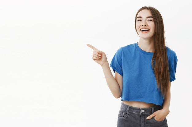 Ritratto di bruna femmina di bell'aspetto felice divertito in maglietta ritagliata blu alla moda che punta a sinistra e che ride gioiosamente divertendosi a discutere di spazio copia divertente o posto dove rilassarsi sul muro grigio