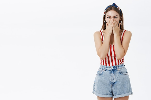 Portrait of amused popular pinup european woman in striped top and denim shorts chuckling covering mouth with palms