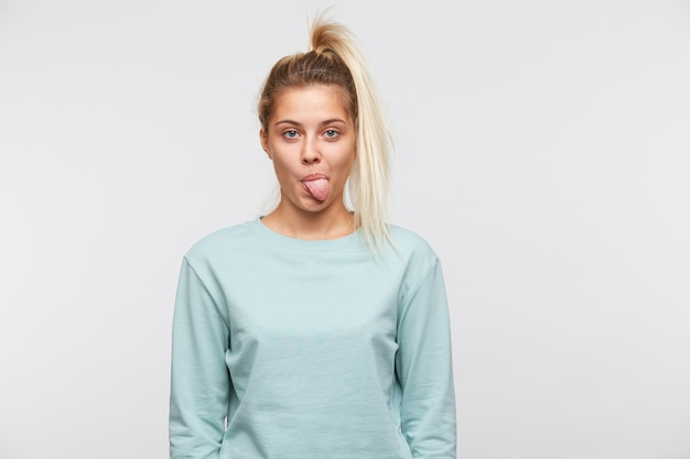 Portrait of amusing cute young woman with blonde hair and ponytail wears blue sweatshirt shows tongue and having fun