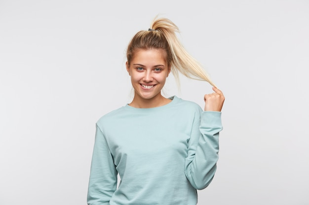 Portrait of amusing cute young woman with blonde hair and ponytail wears blue t shirt