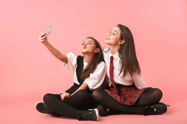 Portrait of amusing girls in school uniform using mobile phones for selfie photos, while sitting on floor isolated over red wall