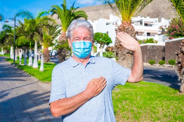 笑顔でカメラを見て、covid-19を防ぐために医療用および外科用マスクを着用している成熟した男性の肖像画とクローズアップ-心の手で新しい挨拶