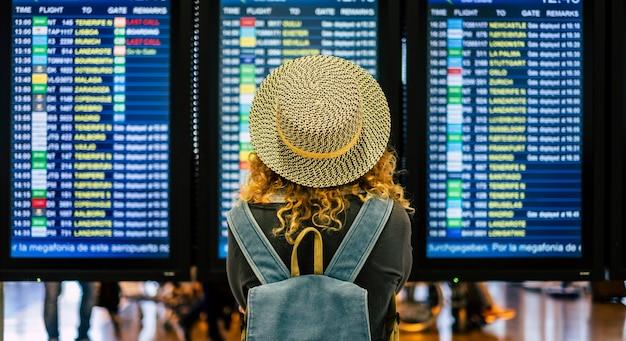 空港での飛行時間をチェックして屋外旅行をし、休暇を楽しむ巻き毛の女性の背中の肖像画とクローズアップ