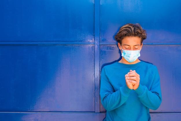 彼の顔に医療とサージカルマスクを祈って身に着けている男のティーンエイジャーの肖像画とクローズアップ-青いセーターと青い背景を身に着けている目を閉じて祈る千年紀