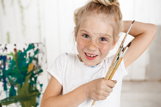 Portrait of angel-like cheerful smiling with teeth child in white morning light in art room, holding in her hand bunch of brushes. little european girl with blond hair looking happy and joyful showing