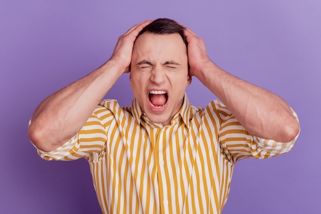 Portrait of angry aggressive guy hands head open mouth scream on violet background