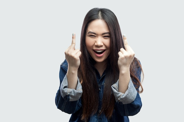 Portrait of angry beautiful brunette asian young woman in casual blue denim jacket standing screaming and looking at camera with middle finger fuck sign. studio shot, isolated on light grey background