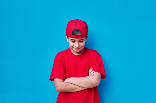 A portrait of angry boy in red cap and t-shirt with closed eyes and looking down