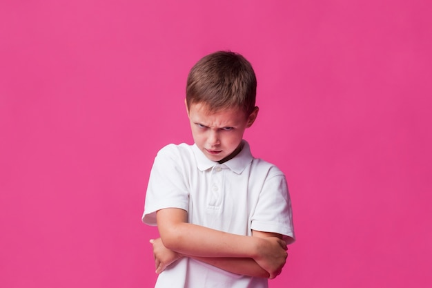 Portrait of angry boy standing over pink backdrop