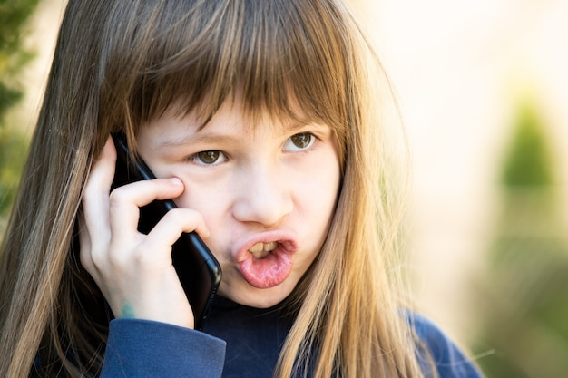 Portrait of angry child girl with long hair talking on cell phone. little female kid having discussion on smartphone. children communication concept.