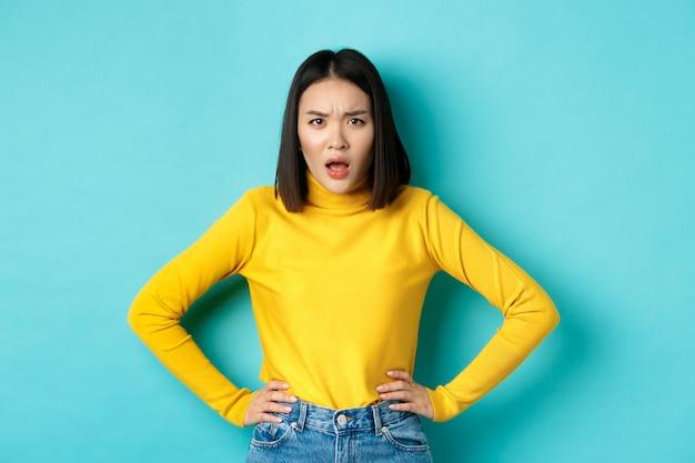 Ritratto di donna asiatica arrabbiata e confusa che fissa frustrata la telecamera, in piedi su sfondo blu.
