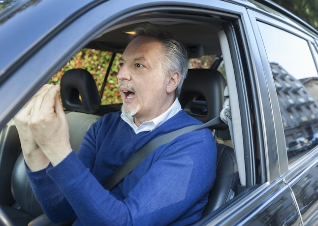 Portrait of an angry driver yelling in his car
