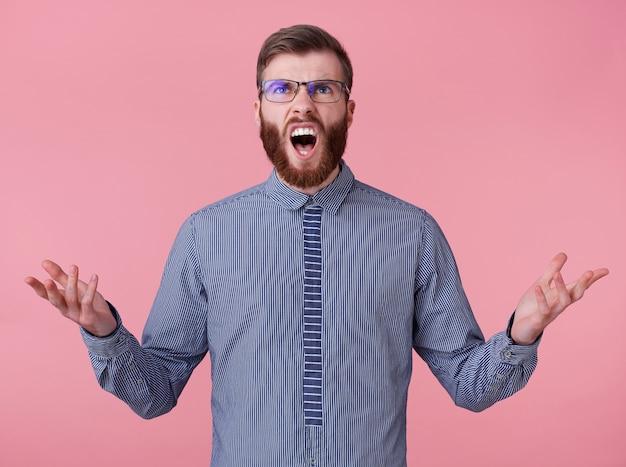 Ritratto di un uomo barbuto rosso bello giovane diabolico arrabbiato con gli occhiali e una camicia a righe, urlando e guarda in alto, in piedi su sfondo rosa.