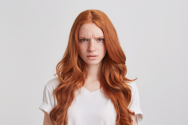 Il ritratto della giovane donna accigliata arrabbiata con capelli rossi ondulati lunghi indossa la maglietta sembra matto