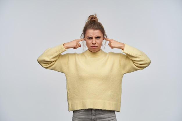 Portrait of angry girl with blond hair gathered in bun. wearing yellow sweater. keeps ears closed with fingers, don't want to hear. watching and frowning at the camera, isolated over white wall