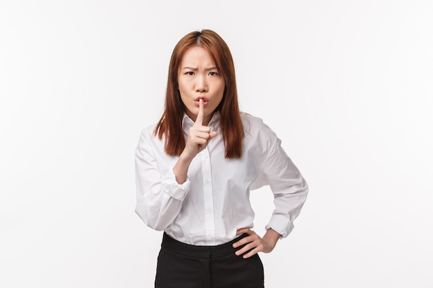 Portrait of angry grumpy asian female boss, employer shushing at person being too loud, make hush gesture with index finger pressed to lips, frowning scolding rude man, quiet please