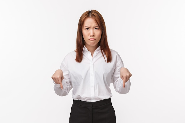 Portrait of angry grumpy asian female entrepreneur scolding employee, pointing down and frowning camera, pouting upset, look here gesture as being disappointed with bad project,