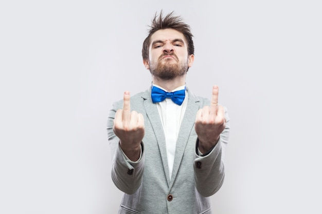 Portrait of angry handsome bearded man in casual grey suit and blue bow tie standing with middle finger fuck sing and looking at camera. indoor studio shot, isolated on light grey background.
