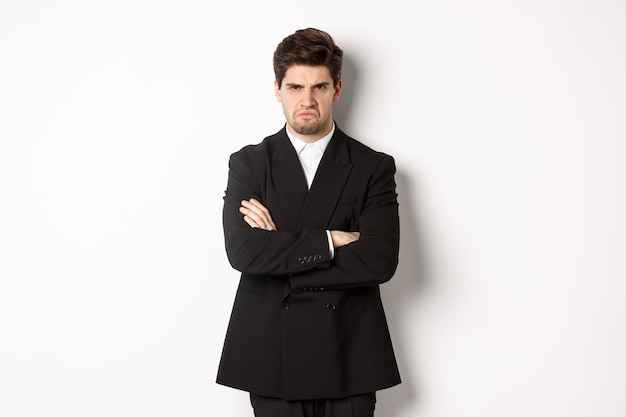Portrait of angry handsome man in black suit, cross arms on chest and looking offended, frowning and pouting, being mad at someone, standing over white background