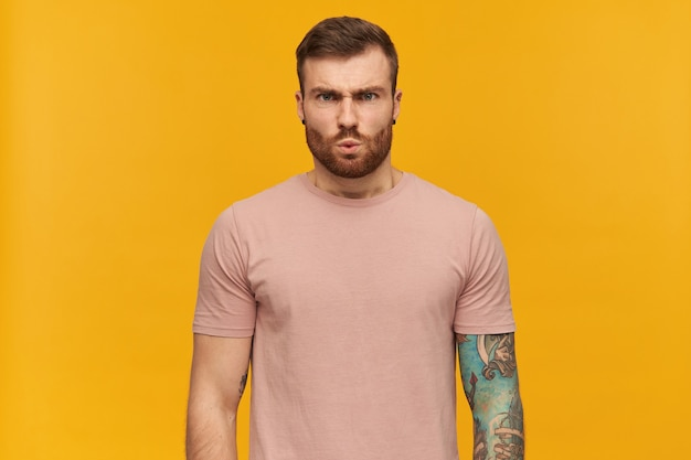 Portrait of angry handsome tattooed young man in pink tshirt with beard looks tensed and irritated over yellow wall standing and looking at front