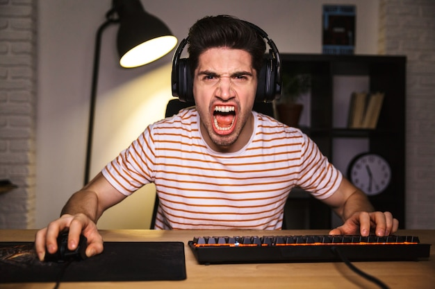Portrait of angry irritated gamer guy screaming while playing video games on computer, wearing headphones and using backlit colorful keyboard