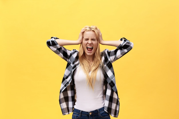 Portrait of an angry irritated woman with hands raised shouting at camera isolated on yellow background