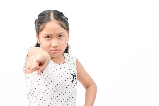 白い壁に分離されたカメラの叫び、感情の顔の概念に指を指している肖像画怒っている子供の女の子