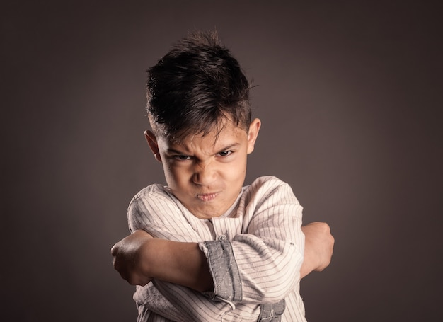 Portrait of angry kid on gray