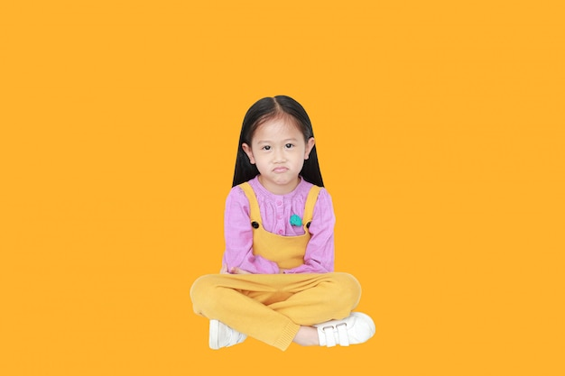 Portrait of angry little asian child girl in pink